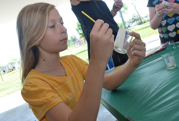 Ainslee Gabriel paints a design on a glass at the May Fair Saturday afternoon at Andrews Park.<br /> Kyle Phillips/The Transcript
