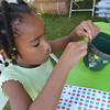 Wilson Terry, 5, puts stickers on a pot she is making at the Adventures in Art tent at the May Fair Satuday afternoon at Andrews Park.<br /> Kyle Phillips/The Transcript