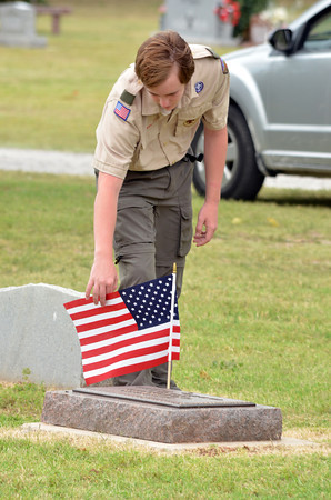 """Tristan White picks up a flag from a grave at Warren Cemetery Sunday afternoon that Boy Scouts from Troop 217 placed on graves for Memorial Day.  To see more photos of Memorial Day celebrations around Norman visit <a href=""""http://photos.normantranscript.com"""">http://photos.normantranscript.com</a>.<br /> Kyle Phillips/The Transcript"""