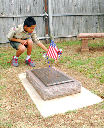 """Walker Pitchlynn picks up a flag from a grave at Warren Cemetery Sunday afternoon that Boy Scouts from Troop 217 placed on graves for Memorial Day.  To see more photos of Memorial Day celebrations around Norman visit <a href=""""http://photos.normantranscript.com"""">http://photos.normantranscript.com</a>.<br /> Kyle Phillips/The Transcript"""