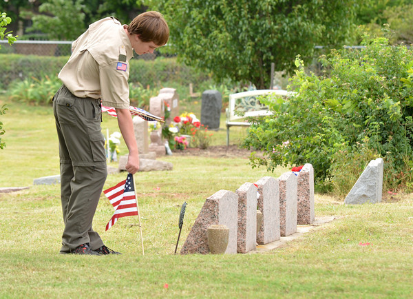 "Tristan White picks up a flag from a grave at Warren Cemetery Sunday afternoon that Boy Scouts from Troop 217 placed on graves for Memorial Day.  To see more photos of Memorial Day celebrations around Norman visit <a href=""http://photos.normantranscript.com"">http://photos.normantranscript.com</a>.<br /> Kyle Phillips/The Transcript"