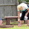 Maryann Lamer places flags around grave sites at Warren Cemetery Sunday afternoon in honor those that have died.<br /> Kyle Phillips/The Transcript