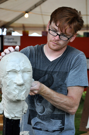 Craig Sawn carves out part of his sculpture during a free demostration at the Midsummers Night's Fair Friday night. Sawn is a sculpture teacher at the Firehouse Art Center. Julie Bragg/ The Transcript