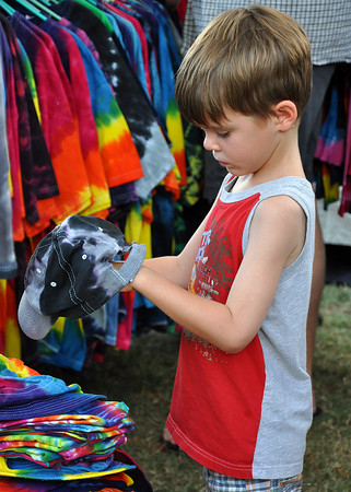 Ben Vishanoff, 7, son of Brenda Vishanoff, gazes at a tie-dye hat for sale in Artist Lori Mendenhall's tent at the Midsummers Night's fair Friday night. Julie Bragg/ The Transcript
