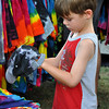 Ben Vishanoff, 7, son of Brenda Vishanoff, gazes at a tie-dye hat for sale in Artist Lori Mendenhall's tent at the Midsummers Night's fair Friday night. Julie Bragg/ The Transcript