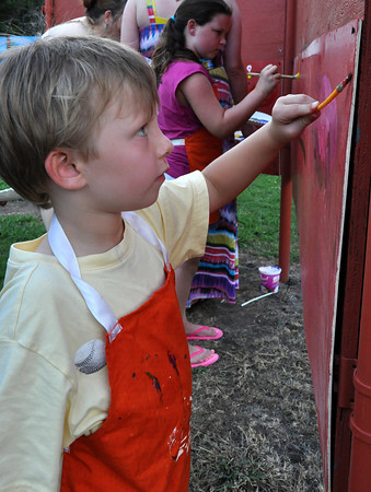Wyatt Dalton, 4 son of Amy Dalton, gets creative with his painting on the art wall at the Midsummers Night's Fair at the Firehouse Art Center Friday night. Julie Bragg/ The Transcript