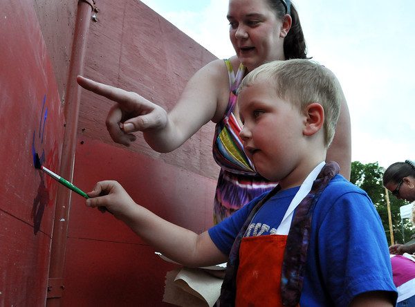 Drake Martin, 4, son of Chelsi Martin paints on the art wall at the Midsummer Night's fair on Friday night. Julie Bragg/ The Transcript