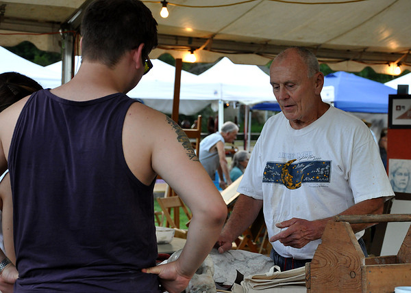 Artist Bill Boettcher gives a presentation of his artwork to art goers at the Midsummer Night's Fair on Friday night. The fair is organized by the Firehouse Art Center. Julie Bragg/ The Transcript