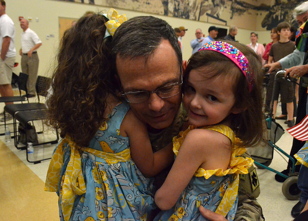 Lt. Col. Rex Duncan hugs his daughters after he arrives home from Afghanistan Wednesday afternoon at the Armed Forces Reserve Center.<br /> Transcript Photo by Kyle Phillips