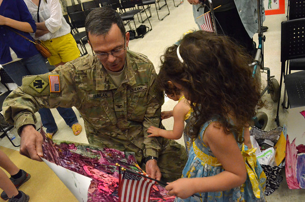 Lt. Col. Rex Duncan looks at a sign his daughters made for him as he returns home from Afghanistan Wednesday afternoon at the Armed Forces Reserve Center.<br /> Transcript Photo by Kyle Phillips