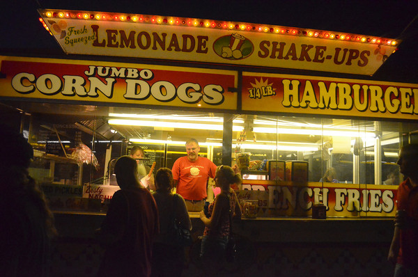 People line up to grab food at one of the many booths Friday night at teh Norman Music Festival.<br /> Transcript Photo by Kyle Phillips