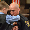 Seven-year-old Aeon Lawton pins his father, Daniel Lawton's, badge on his uniform  during the Norman Police Academy graduation ceremony at Bethal Baptist Church.<br /> Transcript Photo by Kyle Phillips