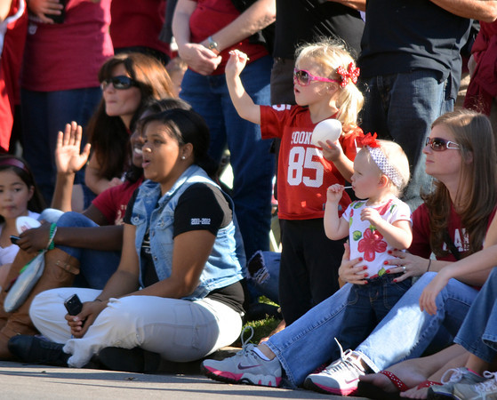Young OU fans wave at parade floats as they pass by  Saturday during the University of Oklahoma homecoming parade.<br /> Kyle Phillips/The Transcript