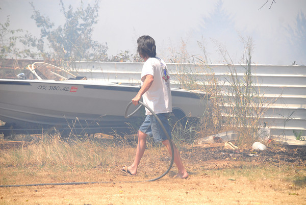 A homeowner grabs his hose to spray the area around his house as a wildfire approaches his property Thursday afternoon on Indian Hills and Sooner Road.<br /> Kyle Phillips/The Transcript