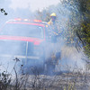 Moore firefighters drive down the fireline looking for hot spots Thursday afternoon as a fire burns in Indian Hills Road and Sooner Road.<br /> Kyle Phillips/The Transcript