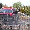 A Moore firefighter leans out of his truck to spray down a hot spot as firefighters from Moore and Norman  battle a fire near Indian Hills Road and Sooner Road.<br /> Kyle Phillips/The Transcript