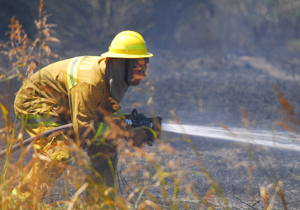A Moore firefighter sprays sprays down hot spots Thursday afternoon as he and other units from Moore and Norman battle a wildfire near Indian Hills Roa and Sooner Road.<br /> Kyle Phillips/The Transcript