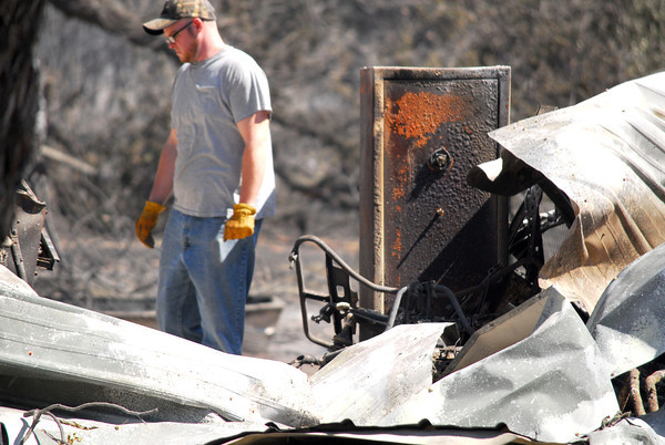 Jarred Fry looks through rubble at his friend's house Saturday afternoon  on Maguire Road as he tries to salvage belongings that were destroyed in the fire that hit Cleveland County Friday.<br /> Kyle Phillips/The Transcript