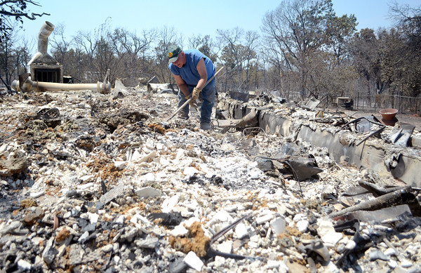 Tommy Walker digs through what was once his sisters house Sunday afternoon as he and other family members try to salvage what they can from the rubble.<br /> Kyle Phillips/The Transcript