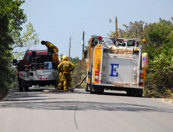 Norman firefighters re-supply a Slaughterville brush pumper on 156th Ave. Saturday afternoon as they try to contain a wildfire that is burning in Cleveland County.<br /> Kyle Phillips/The Transcript