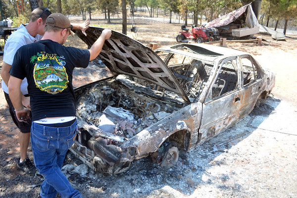 John King, left, and Brandon Pearce look over a burned out car on Pearce's property Sunday afternoon as they check out damage to the family's home caused by the wildfire in Cleveland County.<br /> Kyle Phillips/The Transcript