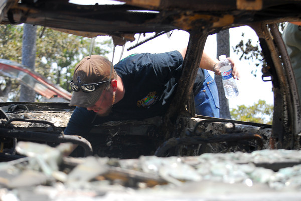Brandon Pearce looks through his mom's car Sunday afternoon, hoping to find something worth saving in the burnt vehicle as he and his family survey their home Sunday afternoon.<br /> Kyle Phillips/The Transcript
