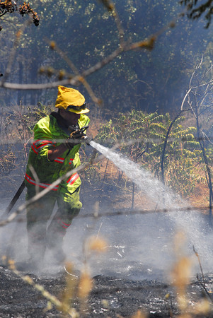 A Cedar Creek firefighter sprays down hot spots along Cemetery Road Friday afternoon as crews try to contain a wild fire in Cleveland County.<br /> Kyle Phillips/The Transcript