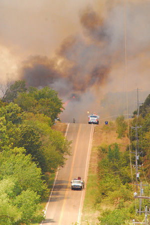 A wild fire jumps over Etowah Road Friday afternoon as a fire burns in south Cleveland County.<br /> Kyle Phillips/The Transcript