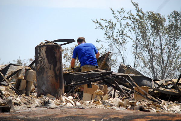 A homeowner digs through the rubble of his house Sunday afternoon after residents were alowed back into their homes to assess the damage from the wildfire that hit Cleveland County over the weekend.<br /> Kyle Phillips/The Transcript