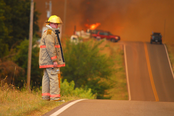 A firefighter waters for traffic as a fire burns in the distance Friday afternoon on Etowah Rd. as a wild fire burns in Cleveland County.<br /> Kyle Phillips/The Transcript