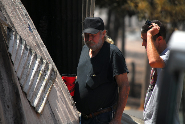 Howard Pearce, left, and John King try to figure out how to get into Pearce's collapsed and burned out shed Sunday afternoon.<br /> Kyle Phillips/The Transcript