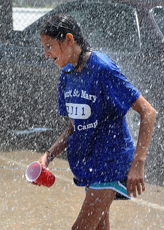 Carmen Kinsey,12, plays in the water sprayed from a Norman Fire Department fire engine on the last day on Totus Tuus on Friday. Children at St. Joseph's Catholic Church learn the ways of the Catholic faith during Totus Tuus.