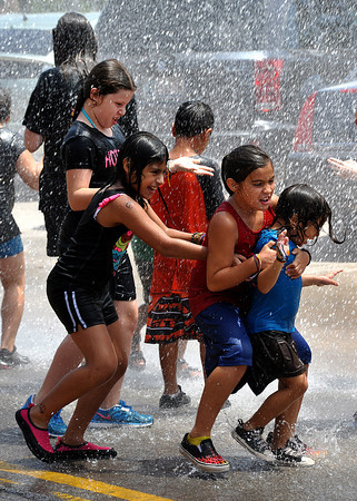 Children play in water provided by a fire engine from the Norman Fire Department on Friday after T