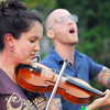 Jen Starsinic plays her fiddle as Evan Harrison Parker plays his bass guitar with the David Mayfield Parade as the band plays a show Sunday at Lions Park during the Summer Breeze Concert Series.<br /> Kyle Phillips/The Transcript