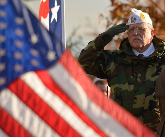VFW Post 88 Chaplain Don Hunter salutes the American Flag Sunday during Norman's Veterans Day ceremony at Reaves Park.<br /> Kyle Phillips/The Transcript