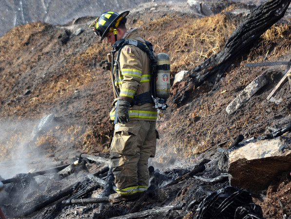 A Norman firefighter stands in a pile of rubble at the waste water treatment plant Wednesday afternoon after a fire burned an area that housed rubber filters at the plant.  No one was hurt in the fire and no buildings were damaged.<br /> Kyle Phillips/The Transcript
