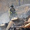 A Norman firefighter looks for any hot spots after a fire was put out at the waste water treatment plant Wednesday afternoon.  The fire burned rubber filters at the plant, as well as the grass around the area.<br /> Kyle Phillips/The Transcript