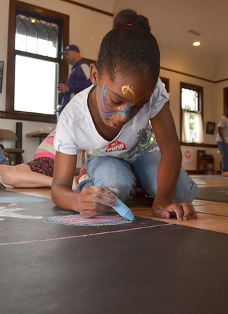 Bailey Irvin, 9, draws a picture for the Sidewalk Chalk Art Contest at the Performing Arts Studio at the Santa Fe Depot Saturday morning.  The contest is part of the CROP Walk event, which will be held on Oct. 7 and will begin and end at Norman's Food & Shelter Inc.<br /> Kyle Phillips/The Transcript
