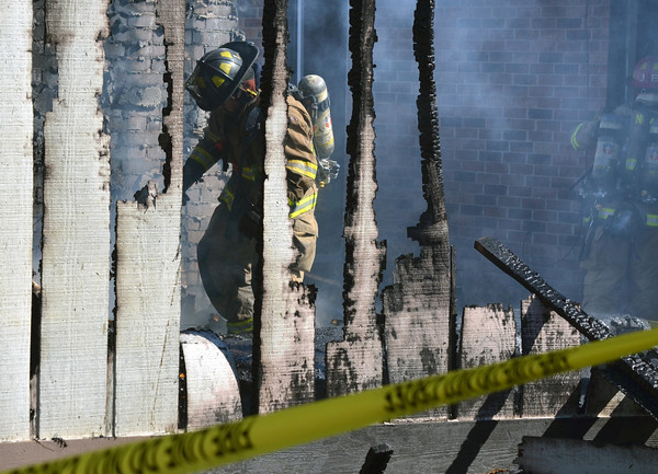 A Norman firefighter picks through debris at 2308 Memphis Dr. firefighters put out a house fire Tuesday afternoon.  The fire started in the detached garage and was fully engulfed and had spread to the house by the time three engines arrives at the scene.  NO one was injured in the fire.  The cause is still under investigation.<br /> Kyle Phillips/The Transcript