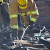 A Norman fire recruit picks through debris at 2308 Memphis Dr. after firefighters put out a house fire Tuesday afternoon.  The fire started in the detached garage and was fully engulfed and had spread to the house by the time three engines arrives at the scene.  NO one was injured in the fire.  The cause is still under investigation.<br /> Kyle Phillips/The Transcript