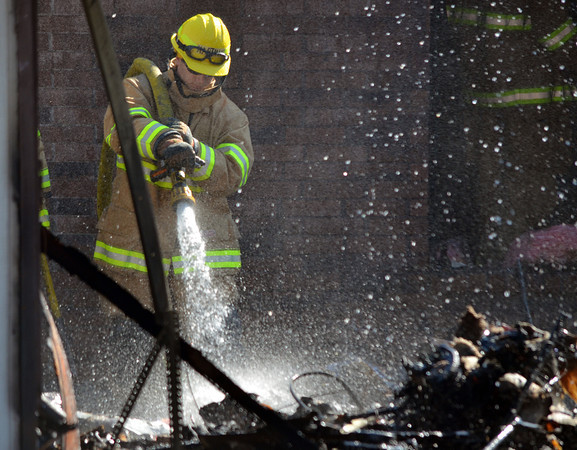A Norman Firefighter sprays down hot spots in a detached garage that caught fire at 2308 Memphis Dr. Tuesday afternoon.  The garage was fully engulfed when fire crews arrived and had spread to the house behind.  No one was injured in the blaze, but the garage is a total loss.  The cause is under investigation.<br /> Kyle Phillips/The Transcript