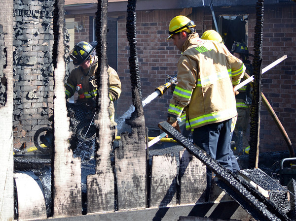A Norman recruit cleans up debris in a detached garage that caught fire at 2308 Memphis Dr. Tuesday afternoon.  The garage was fully engulfed when fire crews arrived and had spread to the house behind.  No one was injured in the blaze, but the garage is a total loss.  The cause is under investigation.<br /> Kyle Phillips/The Transcript