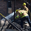 Norman fire recruits help clean up at a house fire at 2308 Memphis Dr. Tuesday after the garage was engulfed in flames spreading the fire to the house behind it.  The detached garage was fully involved when three engines from the Norman fire Department arrived at the scene. No one was injured in the fire.  The cause is under investigation.<br /> Kyle Phillips/The Transcript
