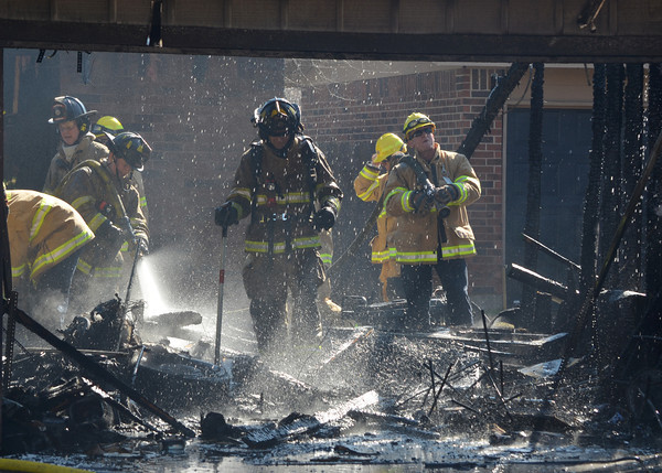 Norman Firefighters pick through debris  in a detached garage that caught fire at 2308 Memphis Dr. Tuesday afternoon.  The garage was fully engulfed when fire crews arrived and had spread to the house behind.  No one was injured in the blaze, but the garage is a total loss.  The cause is under investigation.<br /> Kyle Phillips/The Transcript