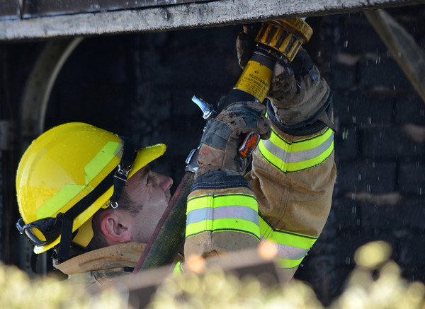 A Norman Fire Recruit sprays down hot spots in a detached garage that caught fire at 2308 Memphis Dr. Tuesday afternoon.  The garage was fully engulfed when fire crews arrived and had spread to the house behind.  No one was injured in the blaze, but the garage is a total loss.  The cause is under investigation.<br /> Kyle Phillips/The Transcript