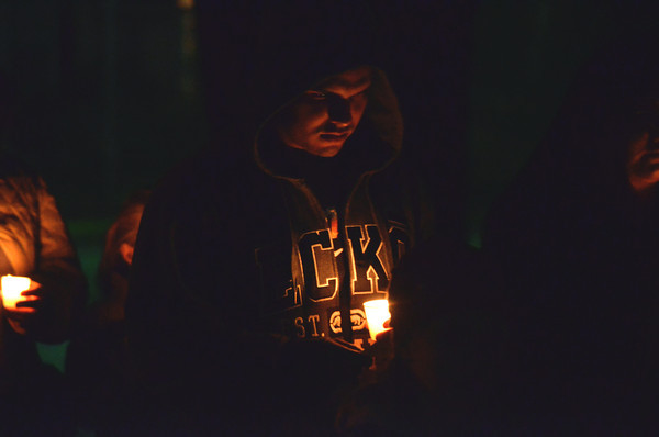 A man covers his candle as she walks with other members of the community Monday evening during a candle light vigil held in response to the school shooting in Conneticut last week.<br /> Kyle Phillips/The Transcript