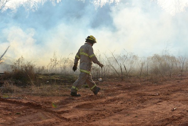 A Noble firefighter walks past a smoldering field along 48th Ave. SE to fight a fire that  broke out in the area Sunday evening .  Units from Noble and Slaughterville responded to the scene stopping the flames before they spread to a neighborhood close by.  No structures wre damaged in the fire.<br /> Kyle Phillips/The Transcript