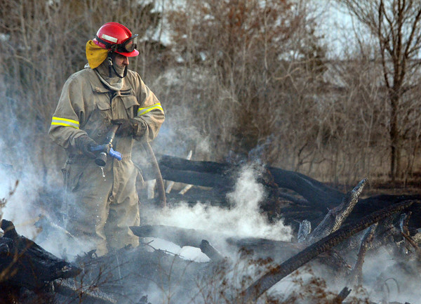 A Slaughterville firefighter sprays down hot spots in a field along 48th Ave. SE after a fire broke out in the area Sunday evening .  Units from Noble and Slaughterville responded to the scene stopping the flames before they spread to a neighborhood close by.  No structures wre damaged in the fire.<br /> Kyle Phillips/The Transcript
