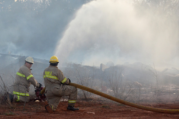 A Noble firefighter sprays down hot spots in a field along 48th Ave. SE after a fire broke out in the area Sunday evening .  Units from Noble and Slaughterville responded to the scene stopping the flames before they spread to a neighborhood close by.  No structures wre damaged in the fire.<br /> Kyle Phillips/The Transcript