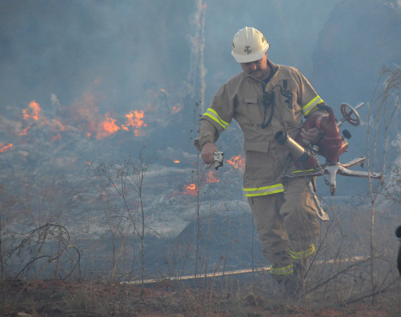 A Noble firefighter carries a hose base to setup to fight a fire that broke out in Noble Sunday evening .  Units from Noble and Slaughterville responded to the scene stopping the flames before they spread to a neighborhood close by.  No structures wre damaged in the fire.<br /> Kyle Phillips/The Transcript